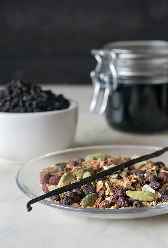Bowl of colorful whole spices, pantry jar of elderberry syrup and displayed elder berries.