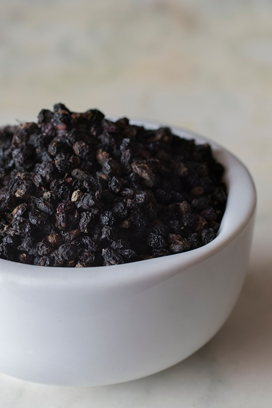 dried elderberries in a white bowl on a white table