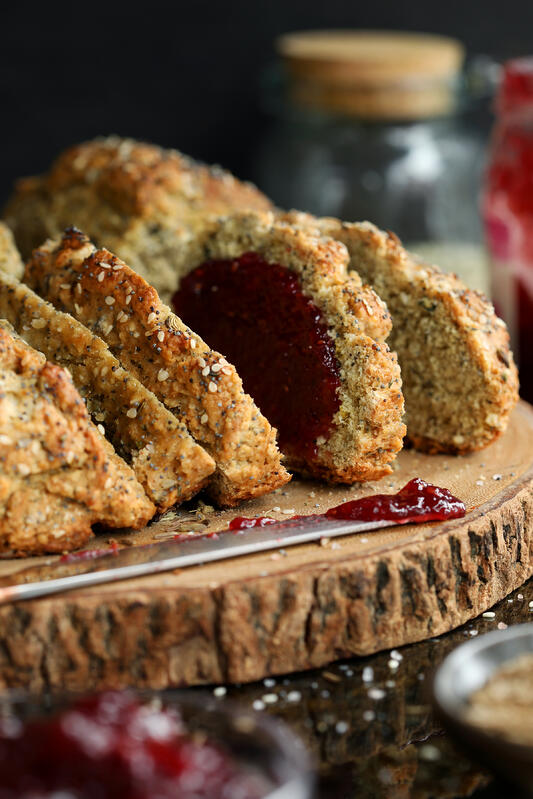 Irish soda bread on a wooden cutting board with a ruby red jam spread. Crunchy soda bread covered in nutritious seeds.