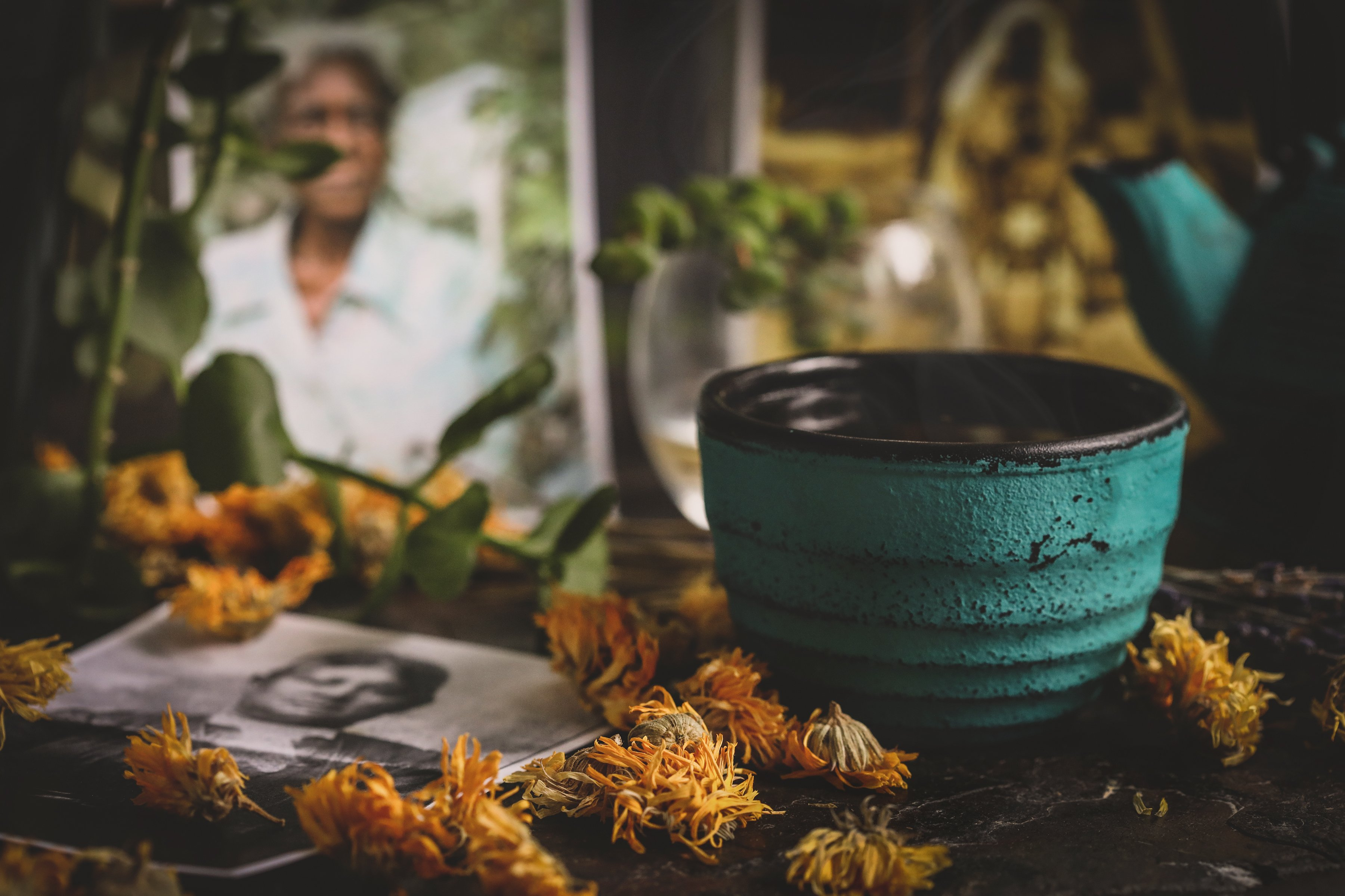 Cast Iron tea cup with flowers and historical photos of folk herbalists of color.