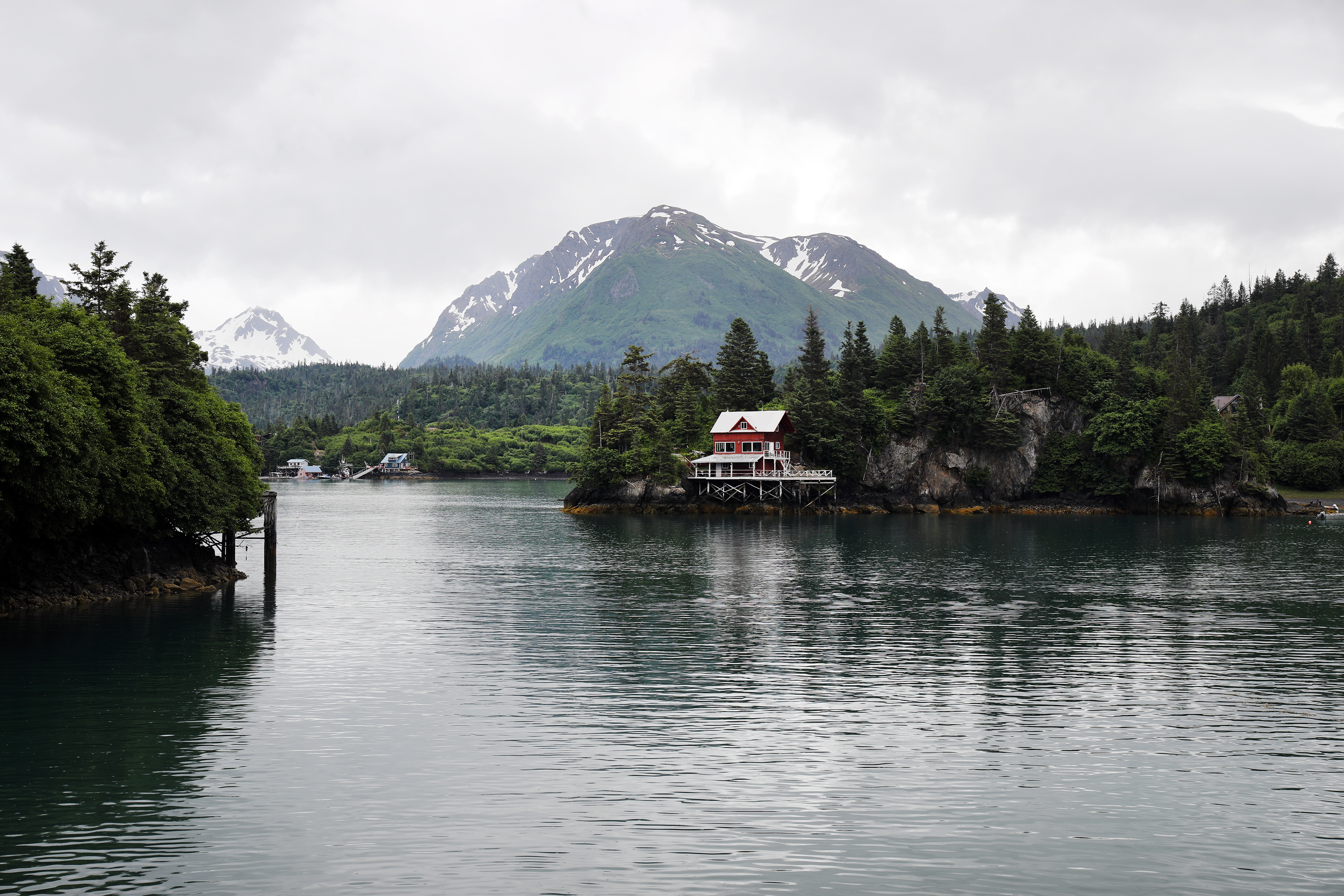 Picture of lake with snow capped mountains in background and modest water front property in Alaska.
