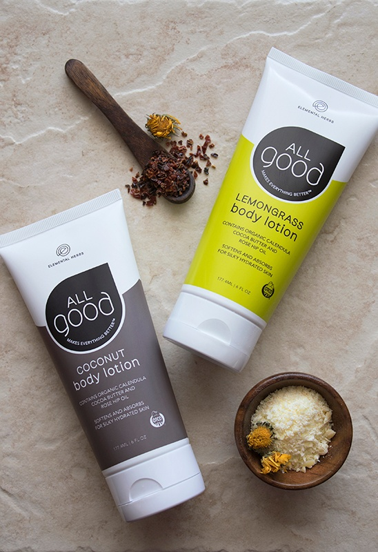 Two flavors of All Good body lotion with bowl and spoon of dried herbs and coconut