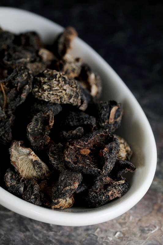 Dried amla is a dark, blackish color. A white bowl is filled with dried amla fruits.