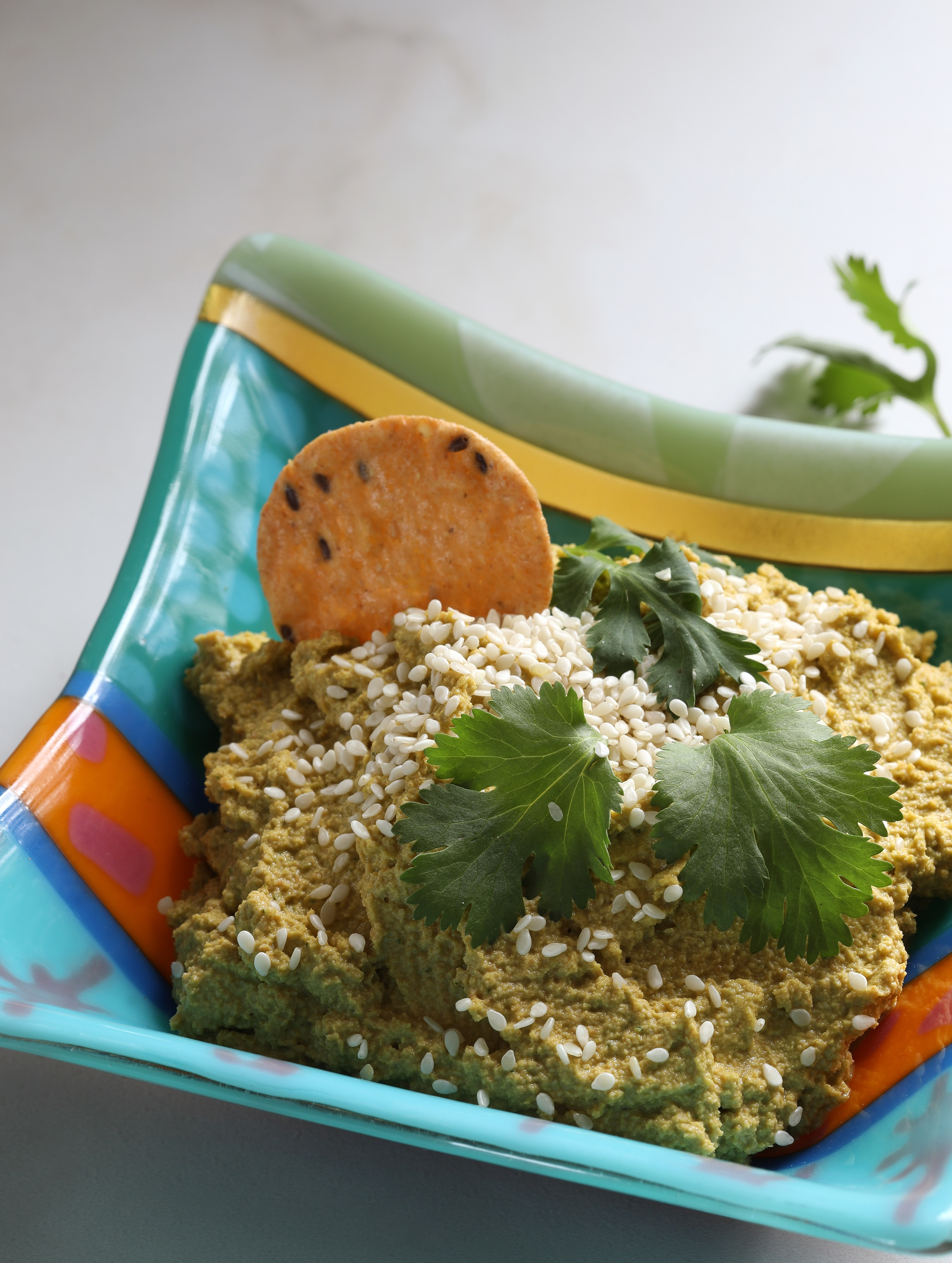 Vegan Carrot Cashew Dip in bowl with sesame seeds and cilantro sprinkled on top