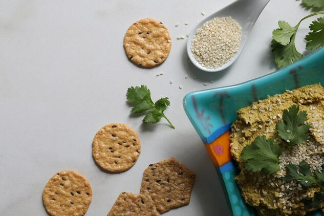Crackers and spoon of sesame seeds and cilantro leaves on counter next to bowl of carrot veggie dip