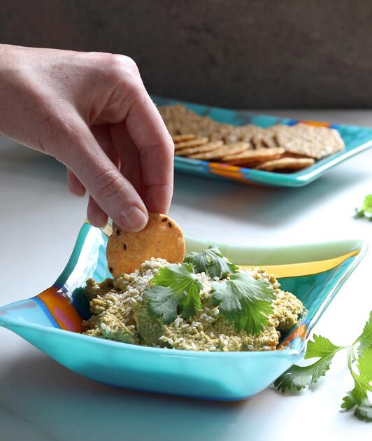 Hand reaching for dip with cracker in blue bowl