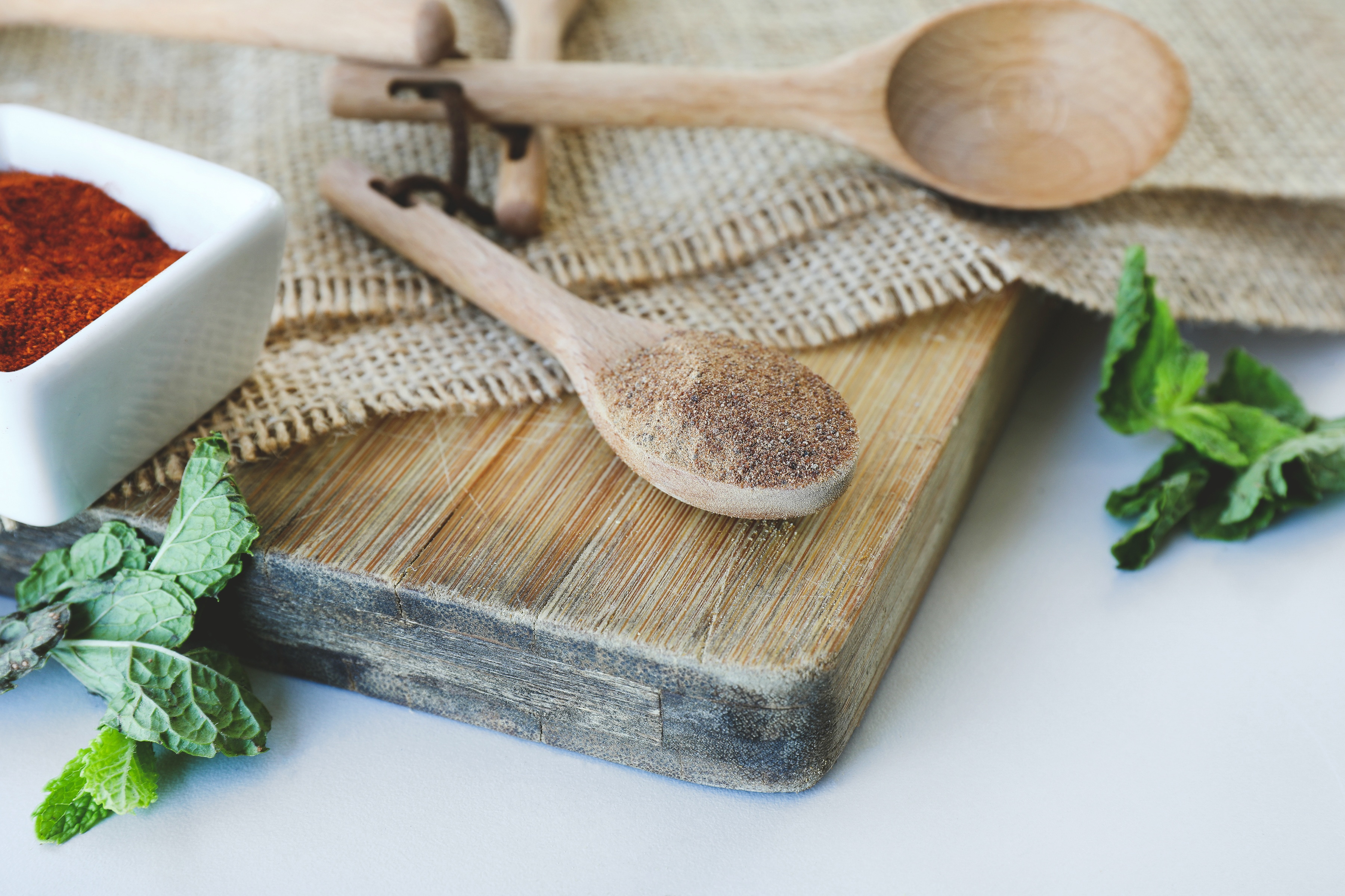 Wooden spoon filled with amla powder and other herbs on cutting board