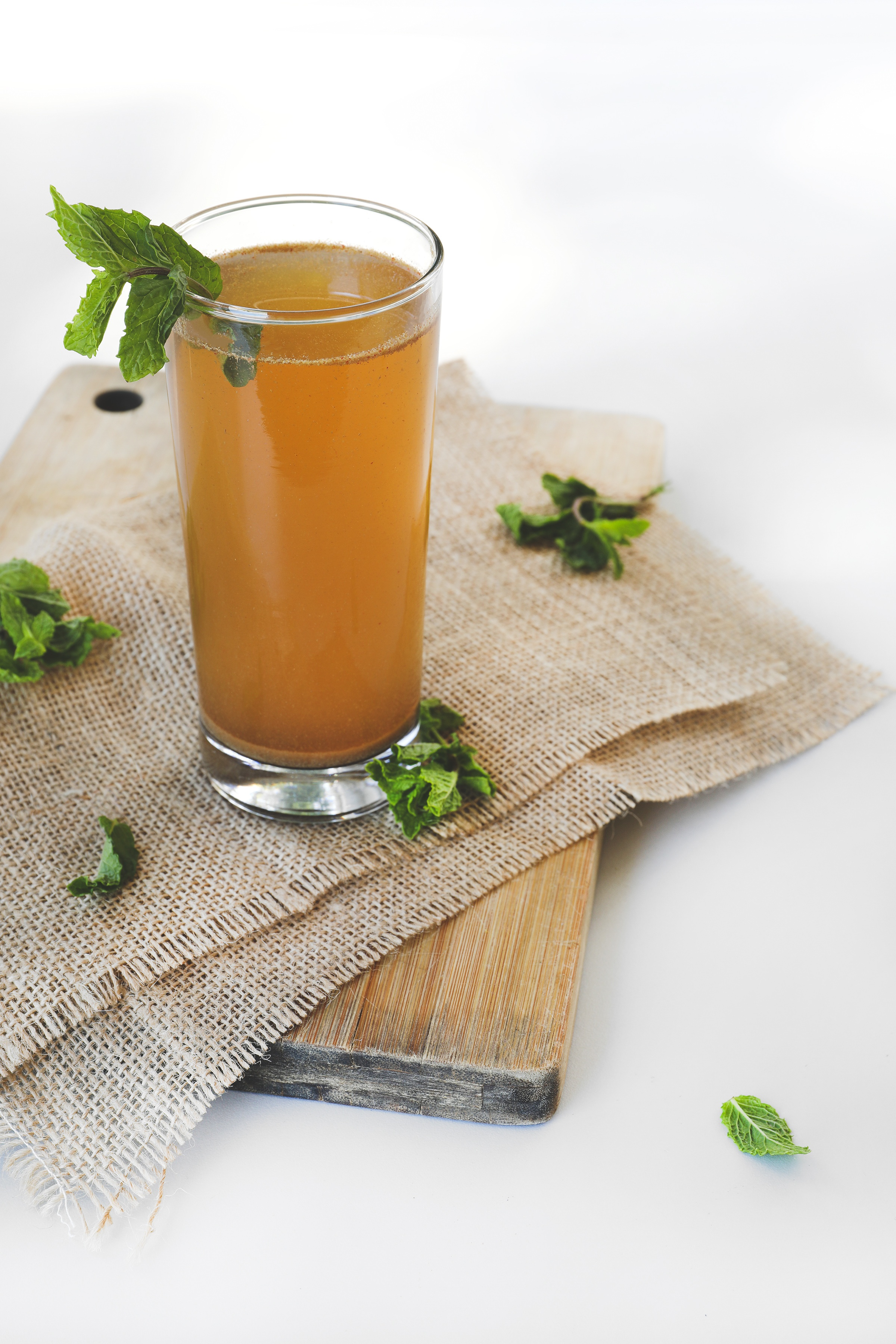 Tall glass with amla drink sitting on burlap napkins on cutting board