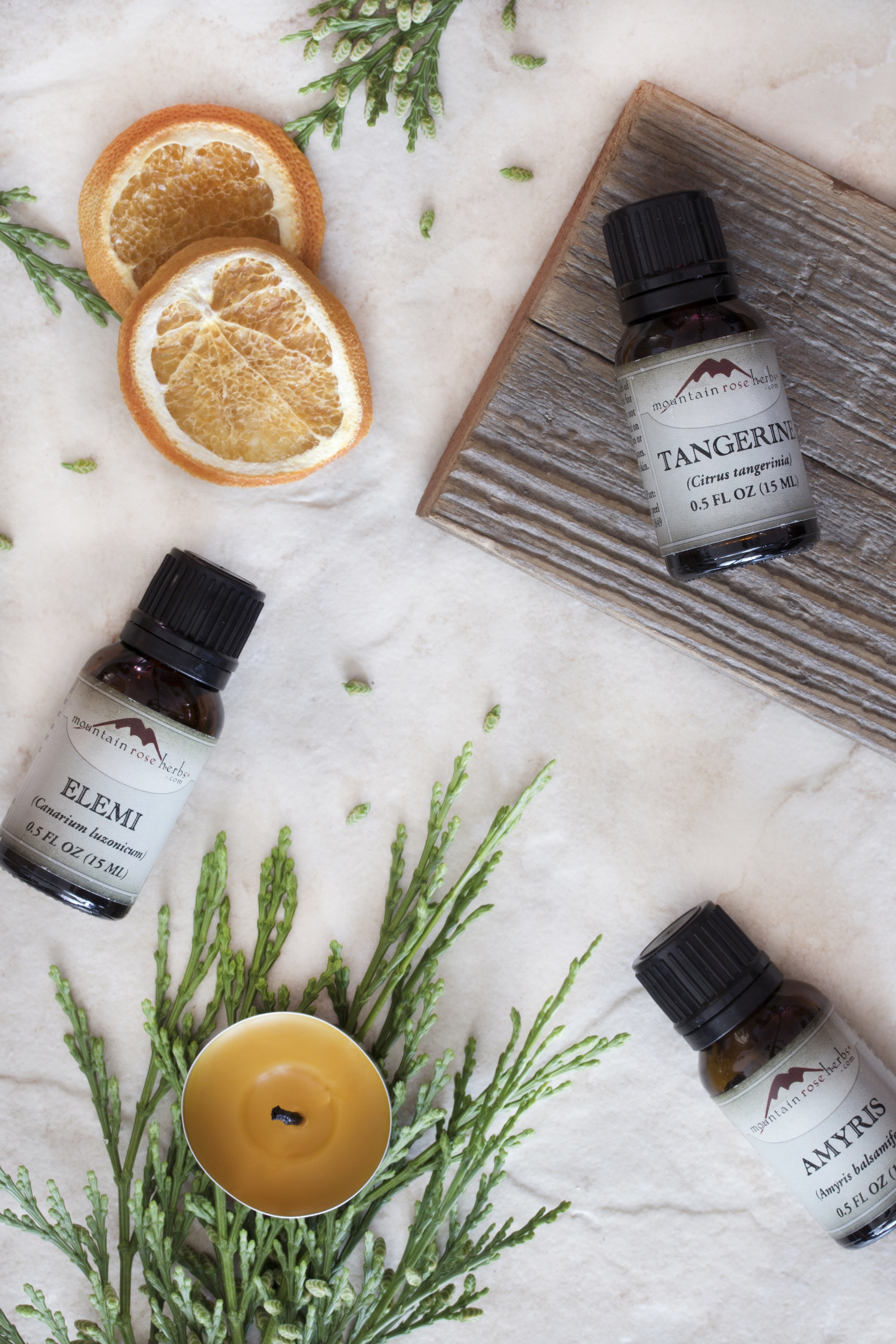 Variety of essential oils, elemi essential oil, tangerine essential oil, and amyris essential oil laying out on counter