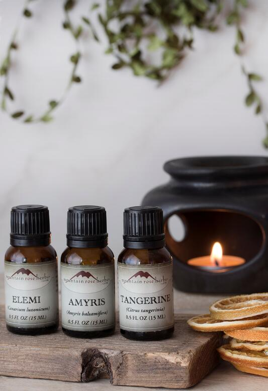 Amyris Essential OIl and other Essential Oils for Diffuse Blend in front of ceramic diffuser