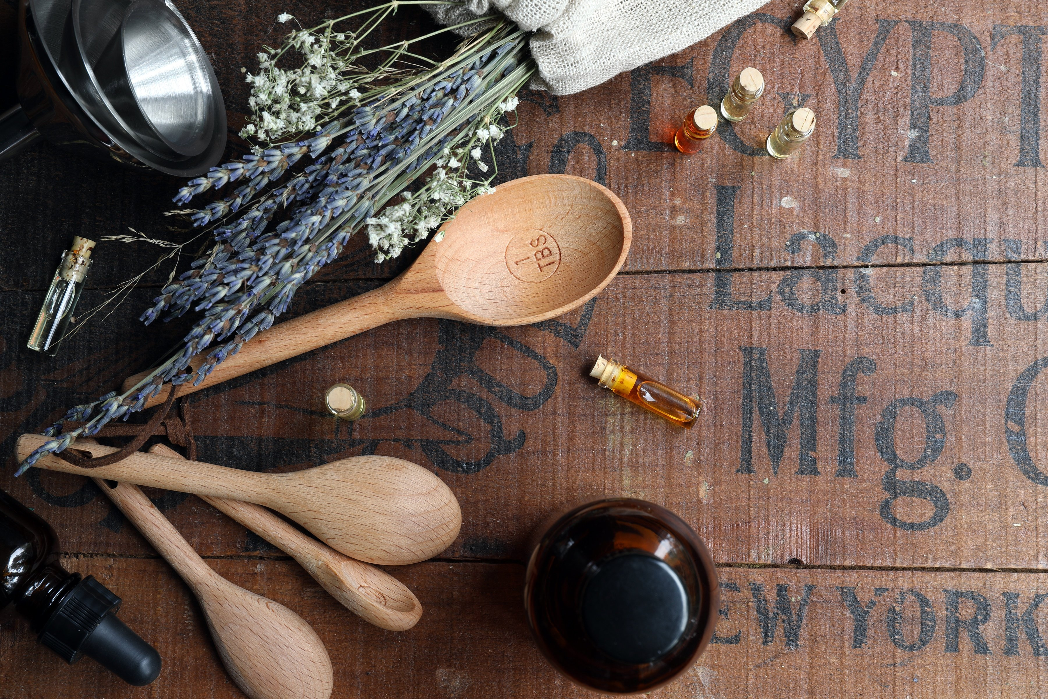 Wooden spoons laying hout year essential oils and dried lavender and other herbal tools