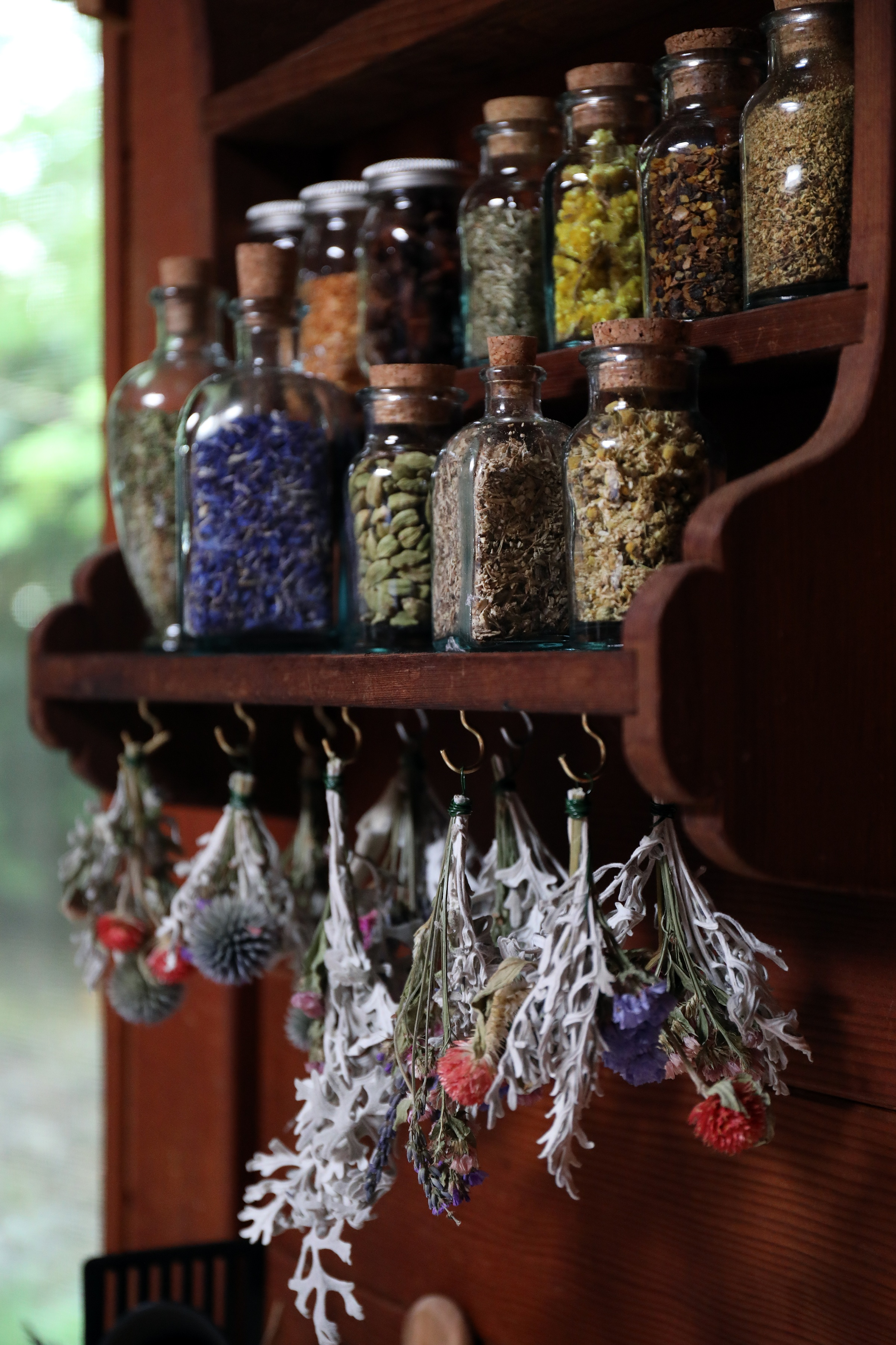 Herbal apothecary shelf with glass cork top bottles filled with dried herbs with hanging dried plants below