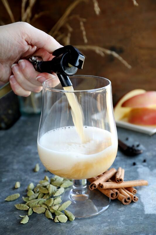 Hand pouring bubbly beverage our of a spout into ornate glass with warm botanicals in background