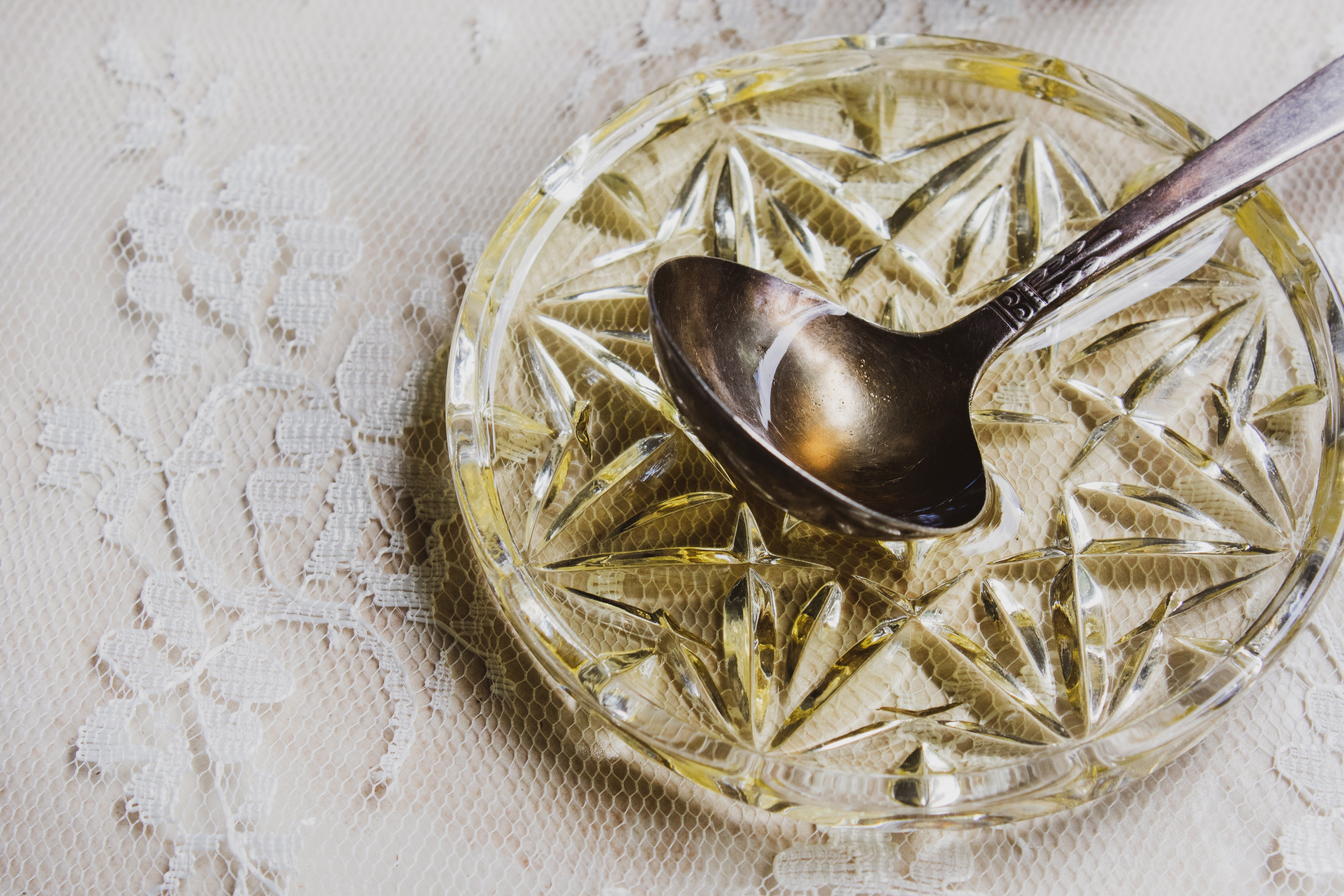 Spoon with argan oil resting on small crystal bowl with argan oil on top of lace counter