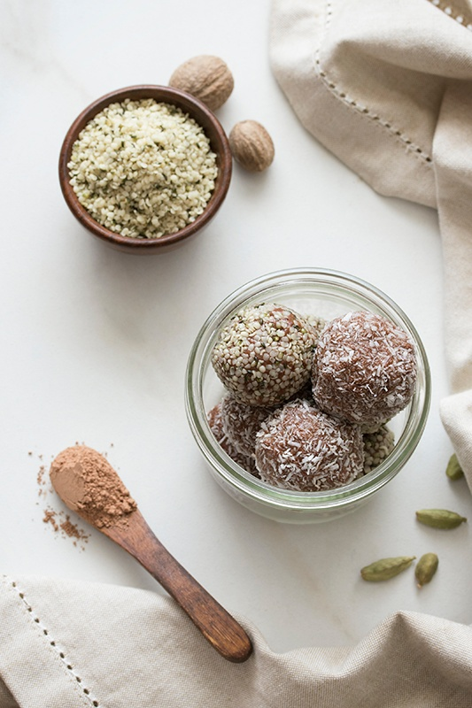 Ashwagandha Chocolate Chai bites in a glass bowl on table cloth with hempseeds and spoon of cacao powder