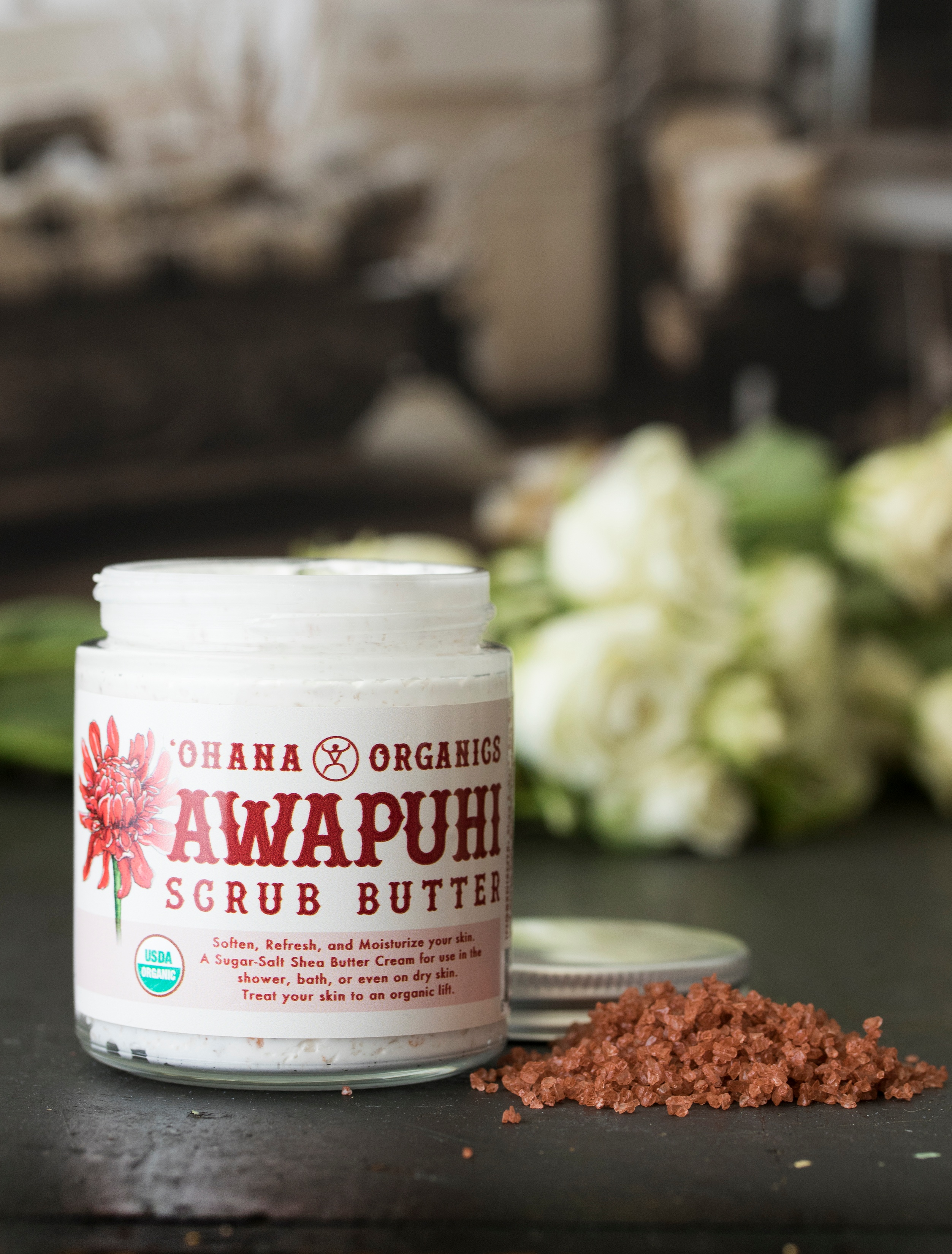 Awapuhi Scrub Butter from Ohana Organics sitting next to pile of red alea salt
