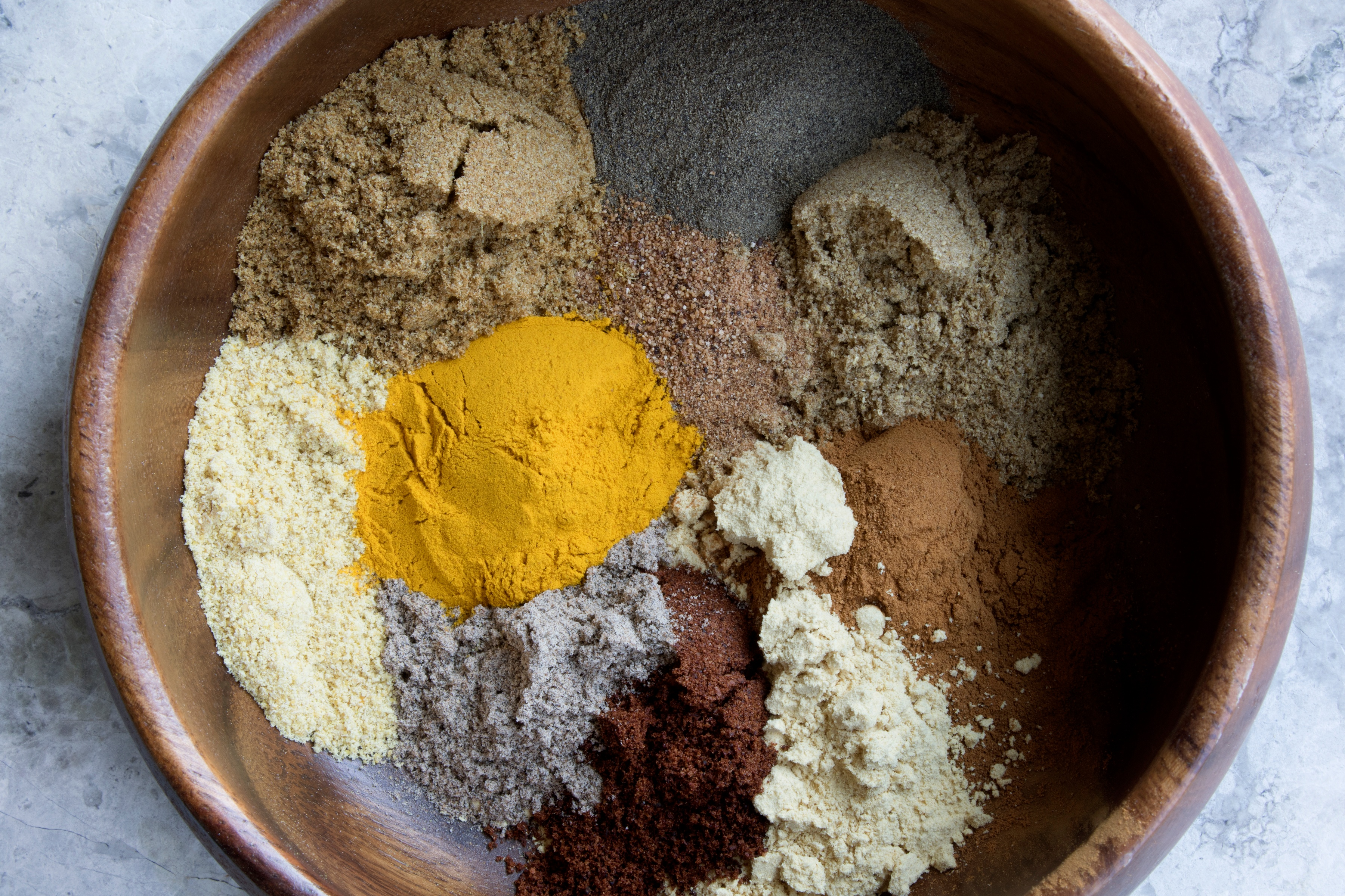 Wooden bowl filled with vibrant colored powdered herbs and spices