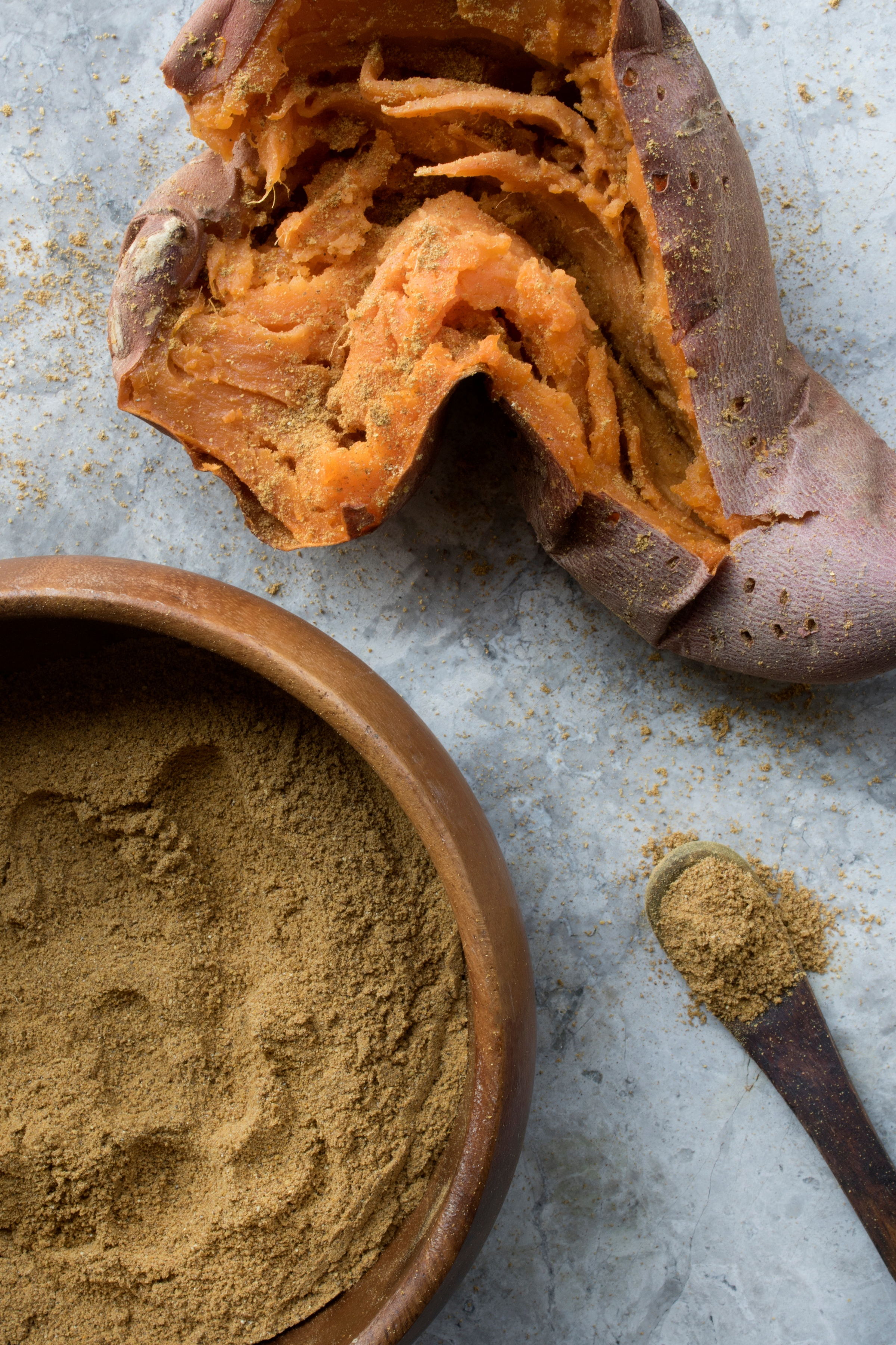 Artistic picture of baked and opened sweet potato with bowl of curry spice blend powder and spoon with same powder.