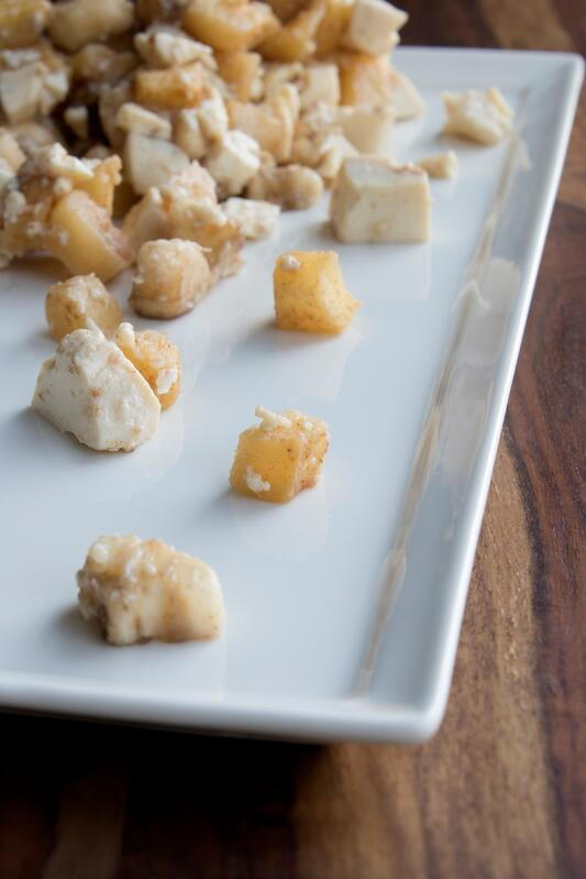 Small pieces of seasoned apples and tofu presented on white plate