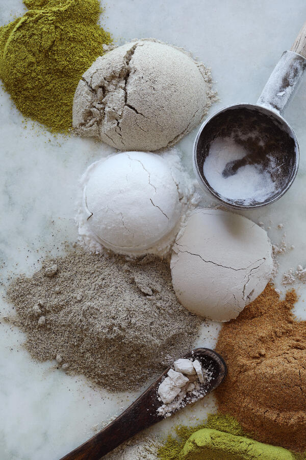 Lumps of cosmetic and herbal powders are assembled with measuring cups and spoons on a white marble counter top.