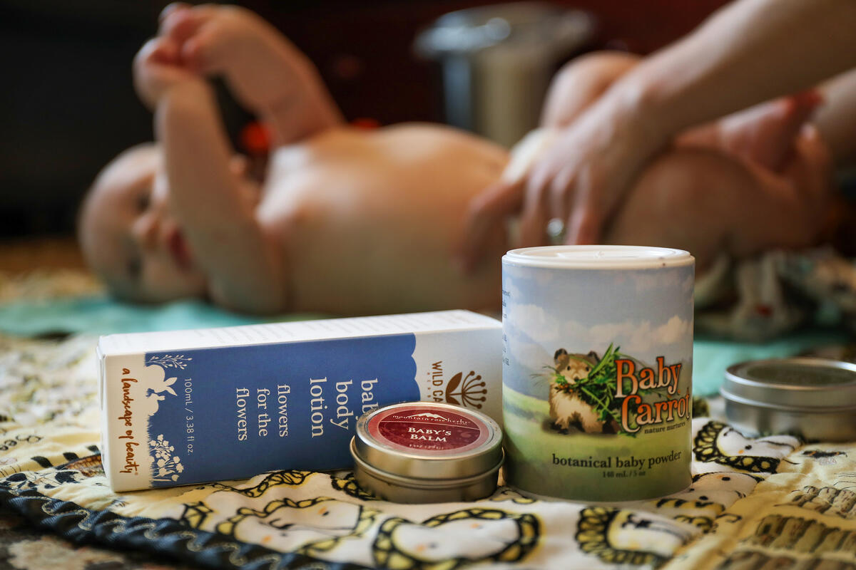 Natural baby products on blanket with baby being changed in background.