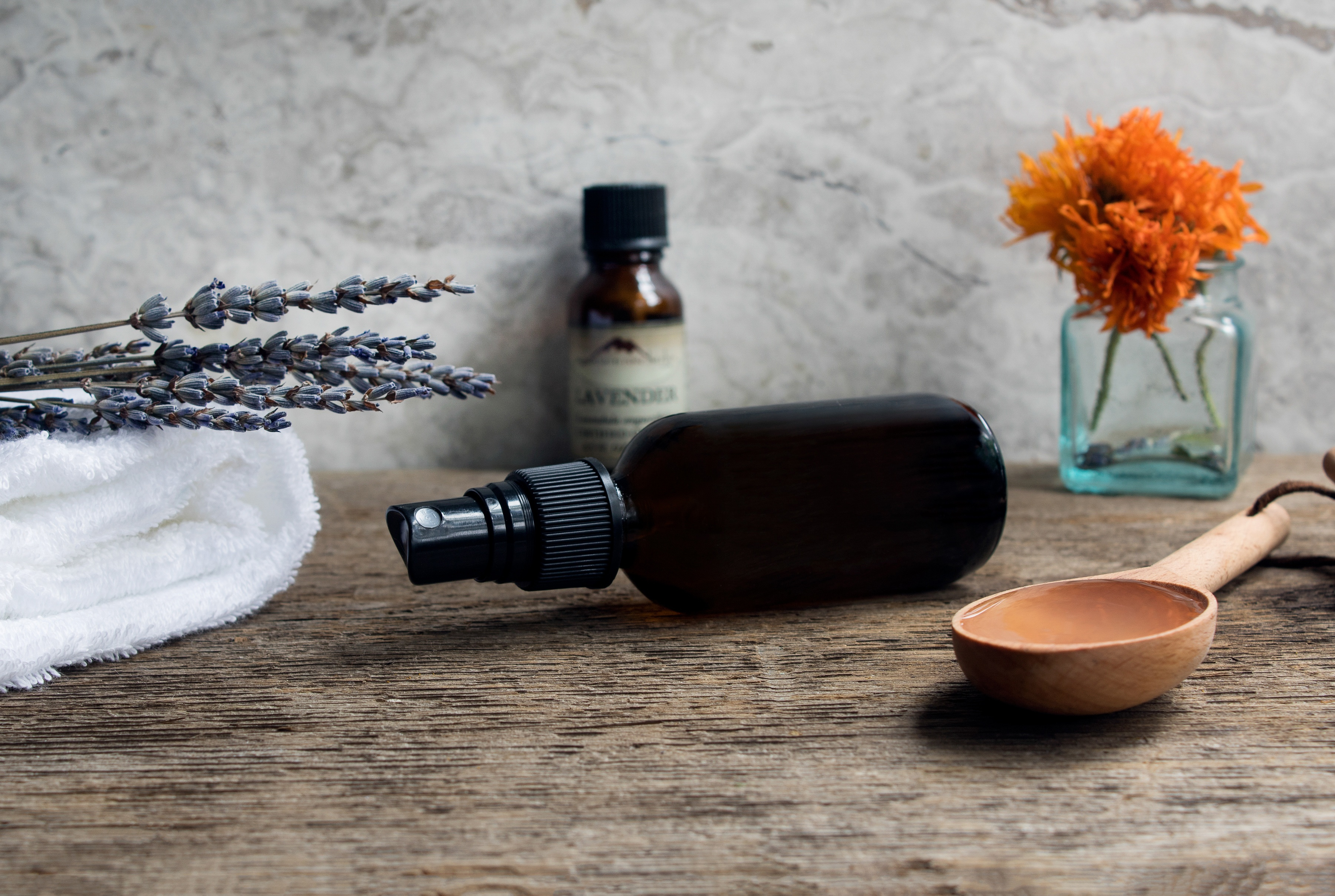 Small mister bottle laying on side on wooden surface next to wooden spoon and lavender