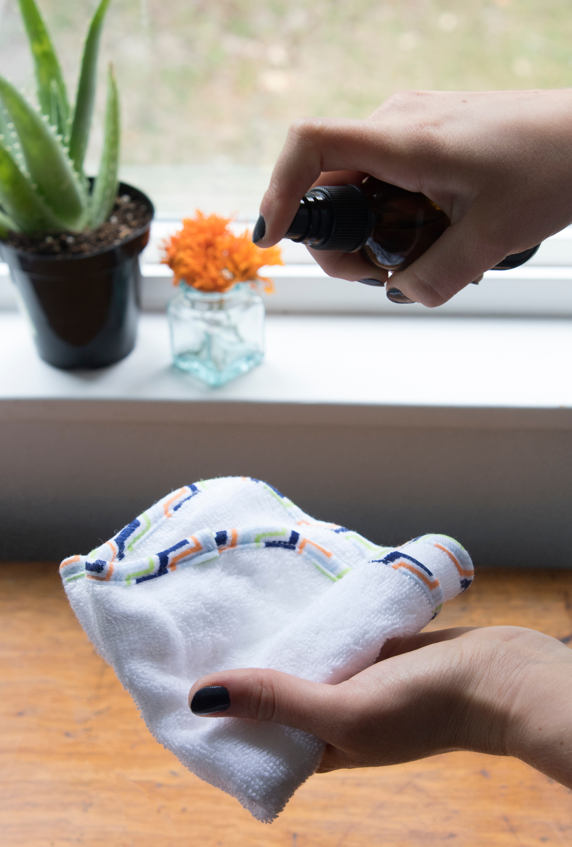 Hand holding baby towel in one hand and baby cleansing spray in the other to make homemade baby wipes