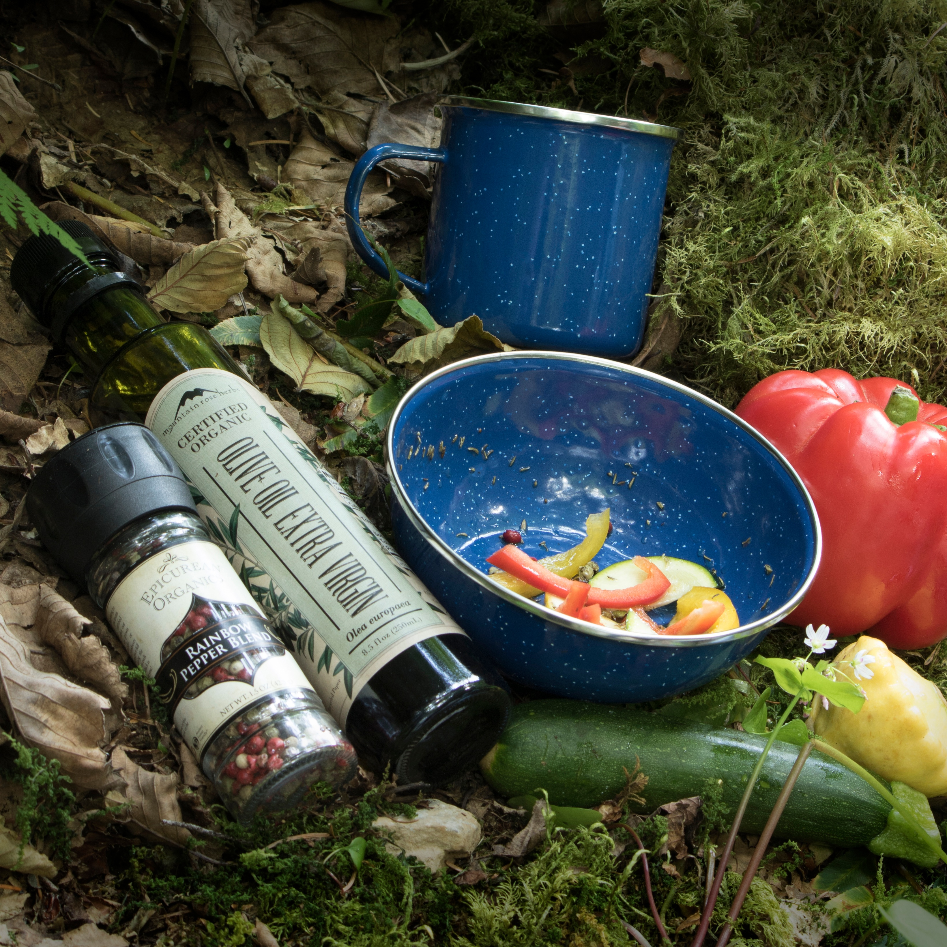 Backpacking and camping bowl and cup outside with vegetables and oil and rainbow peppercorns