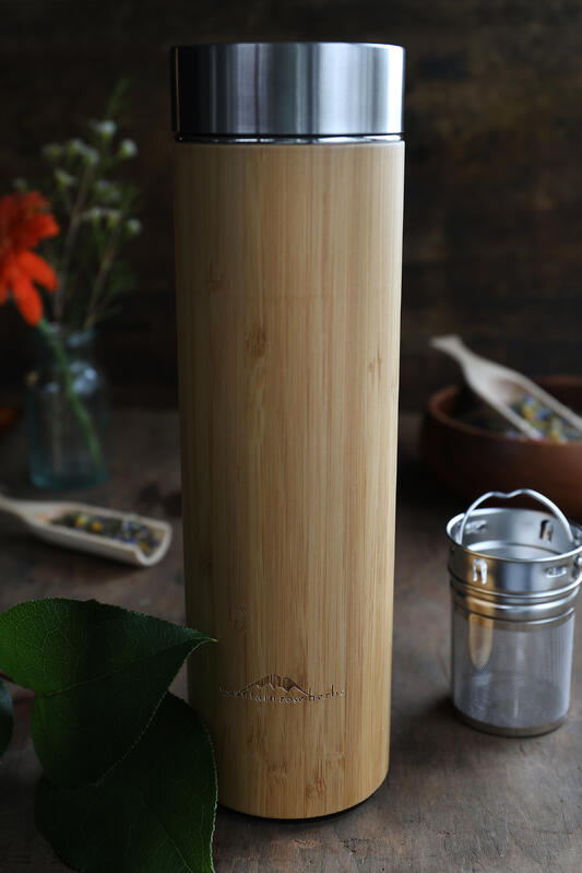 Bamboo and stainless steel tea travel mug with infuser basket on table and fresh plants and herbal teas in background.