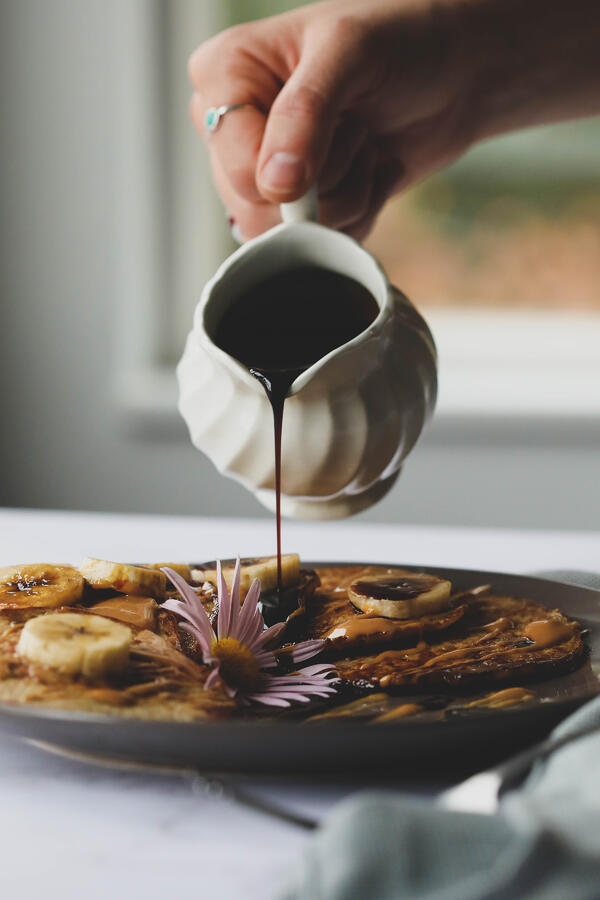 Pouring syrup over banana pancakes.
