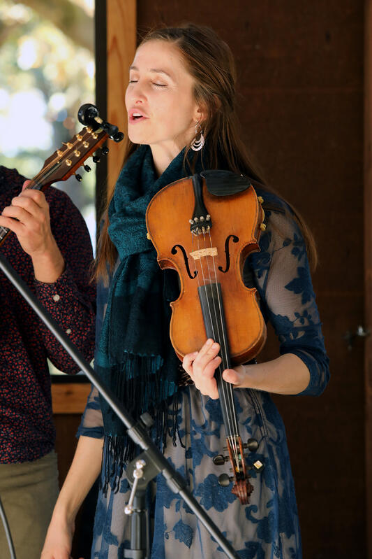 Performer with a violin singing in a band during an event.