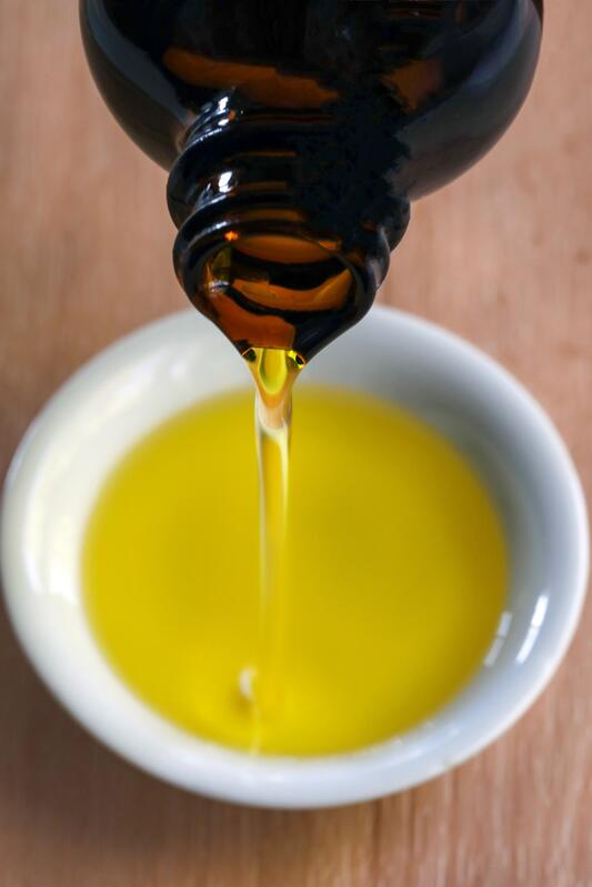 Amber glass bottle of organic baobab oil being poured into white ceramic dish