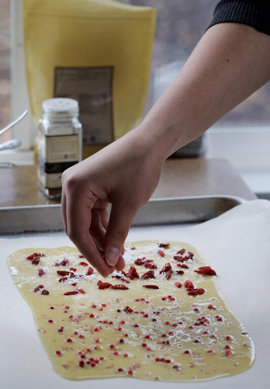 Hand sprinkling toppings on top of cooling homemade white chocolate bark.