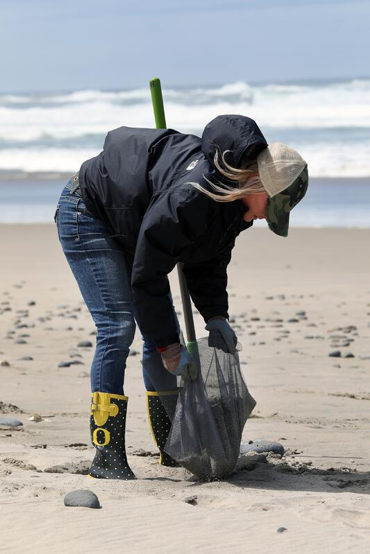 Woman cleaning up trash on a beach on the Oregon Coast