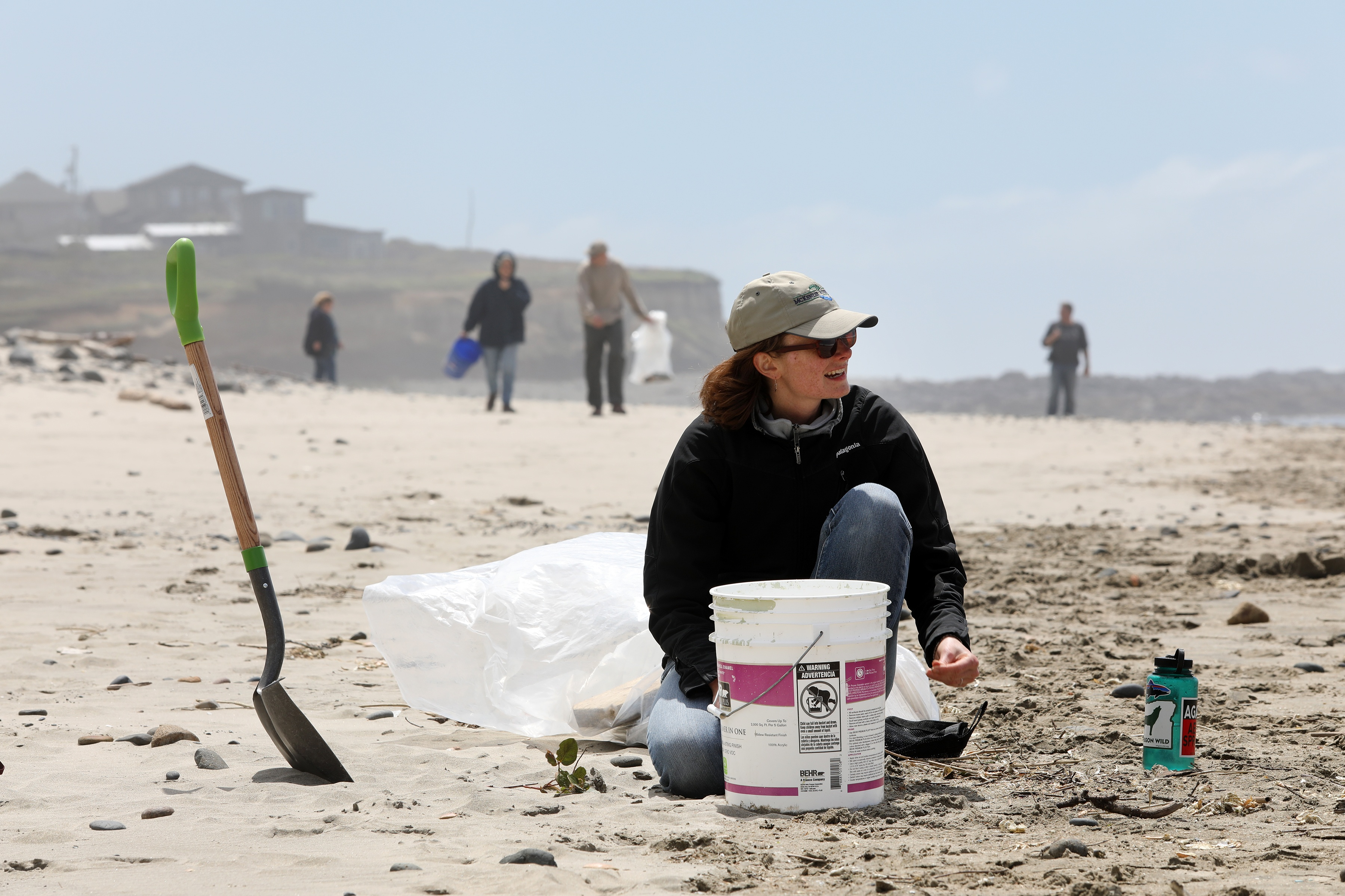 Woman on beach cleaning up trash with volunteer team