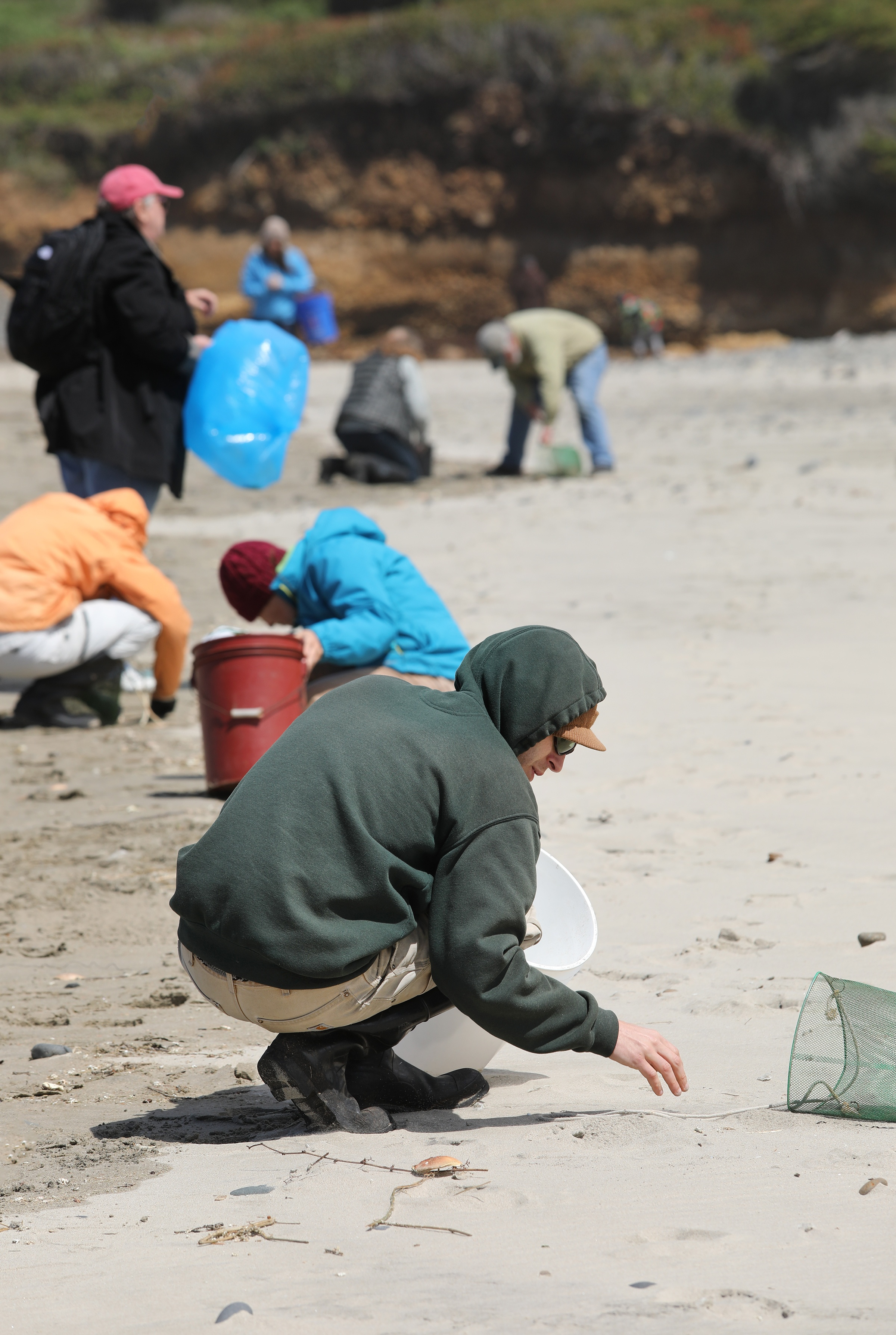Person bending down on sand to pick up trash