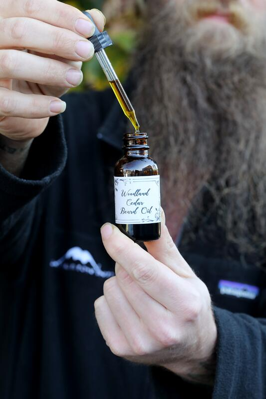 Man's hand using dropper top to display oil with long beard in background.