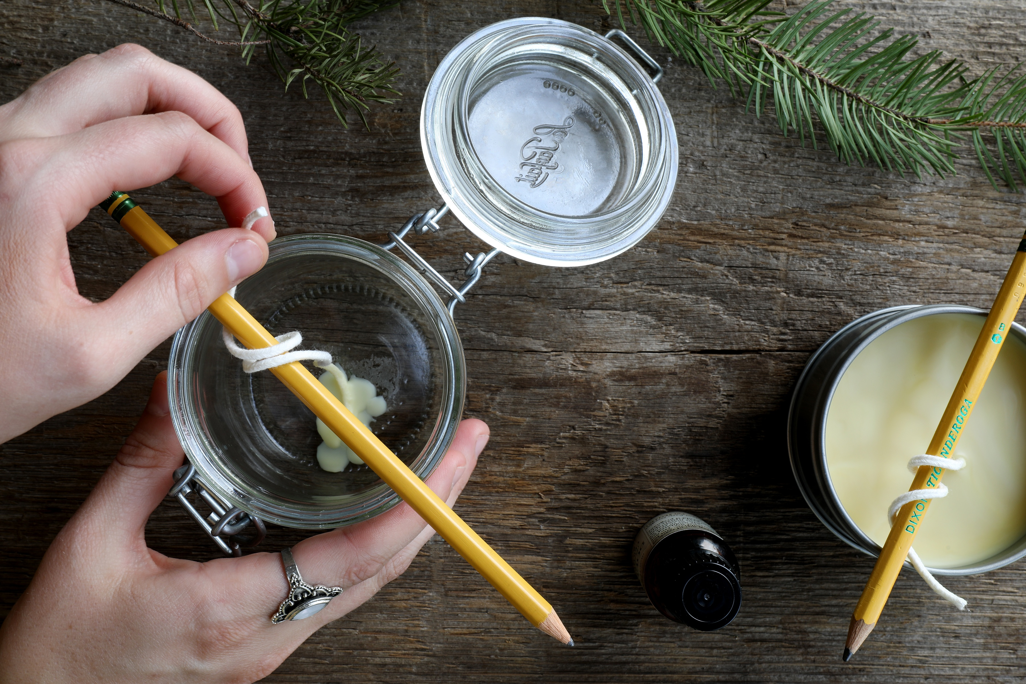 Hands making candles in jars and tins