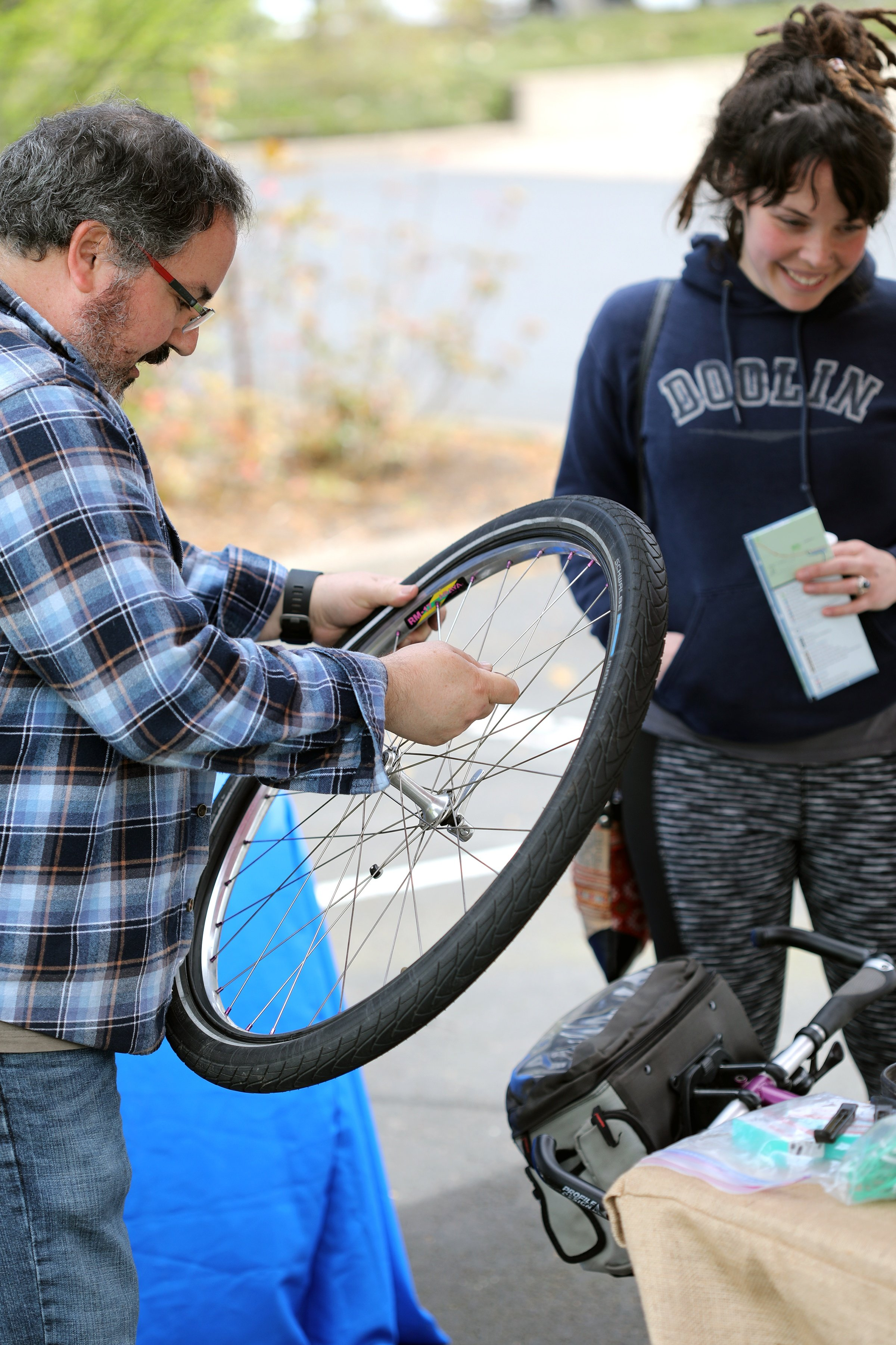 MRH employee with hands on bike wheel for safety check and bike tune up