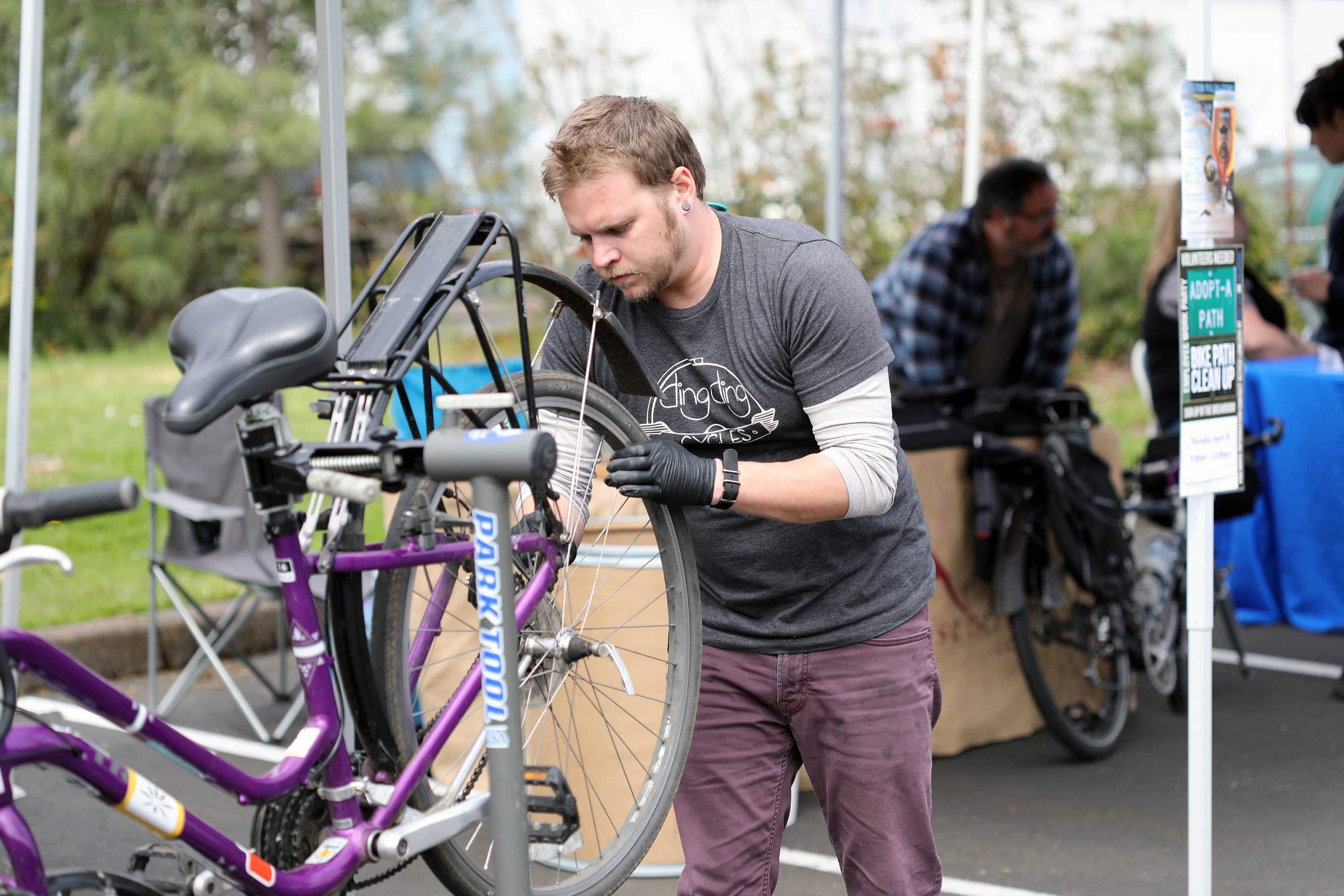 Person holding back tire of bike making adjustments for bike tune up