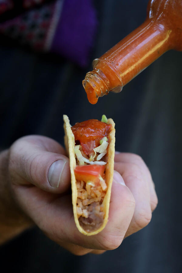 Hand holding a taco while hot sauce is being poured onto it.