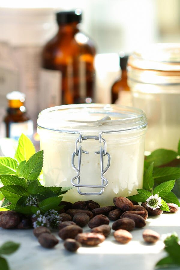 DIY Mint Chocolate Body Buttter in a jar surrounded by ingredients including mint leaves, cacao beans, organic carrier oils, etc.