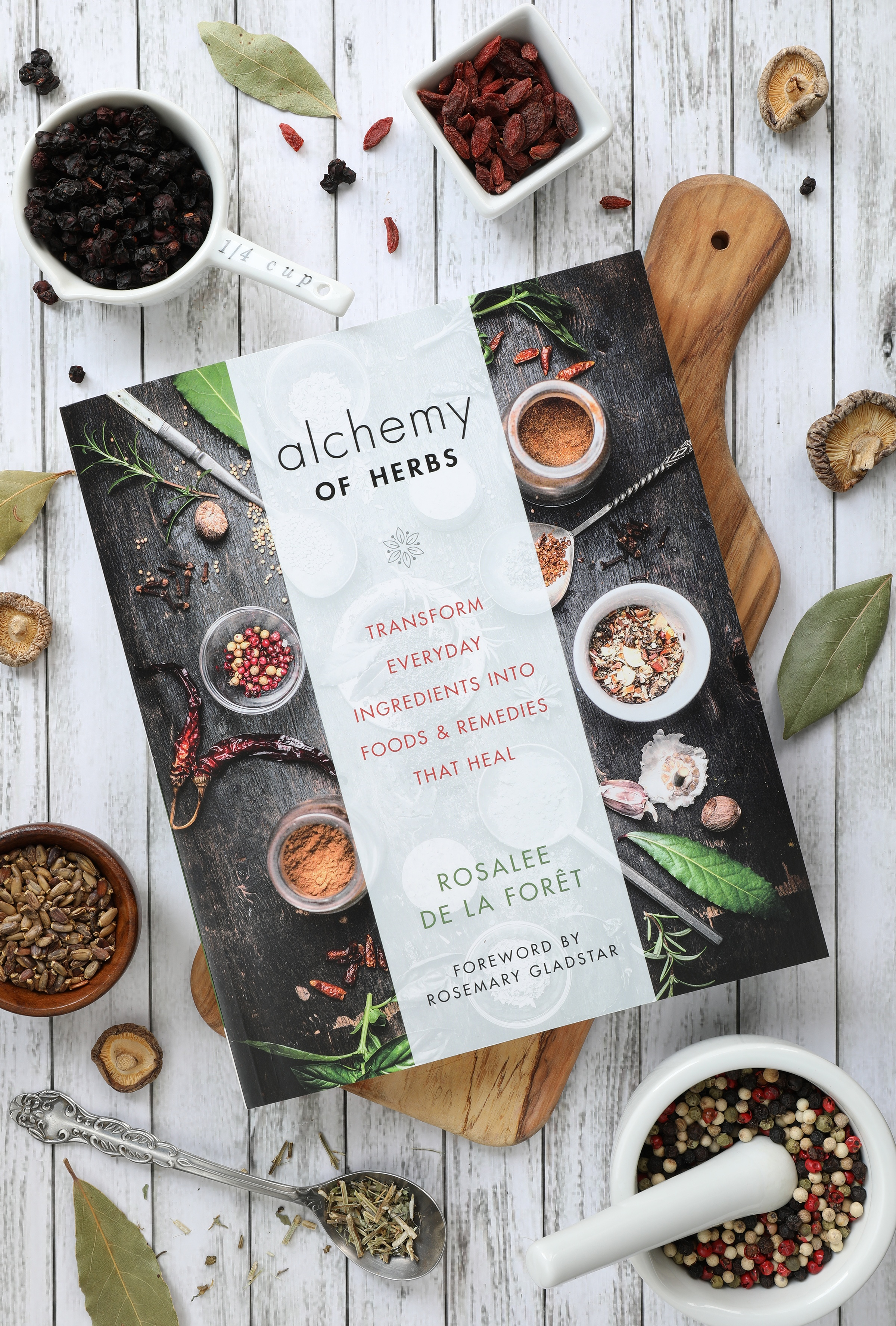 Alchemy of Herbs by Rosalee De La Foret book cover sitting on counter with cooking ingredients and cutting board