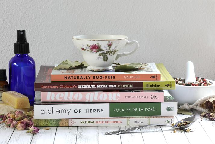 Porcelain China Tea Cup sitting on top of stack of herbal books on desk with herbal DIY ingredients