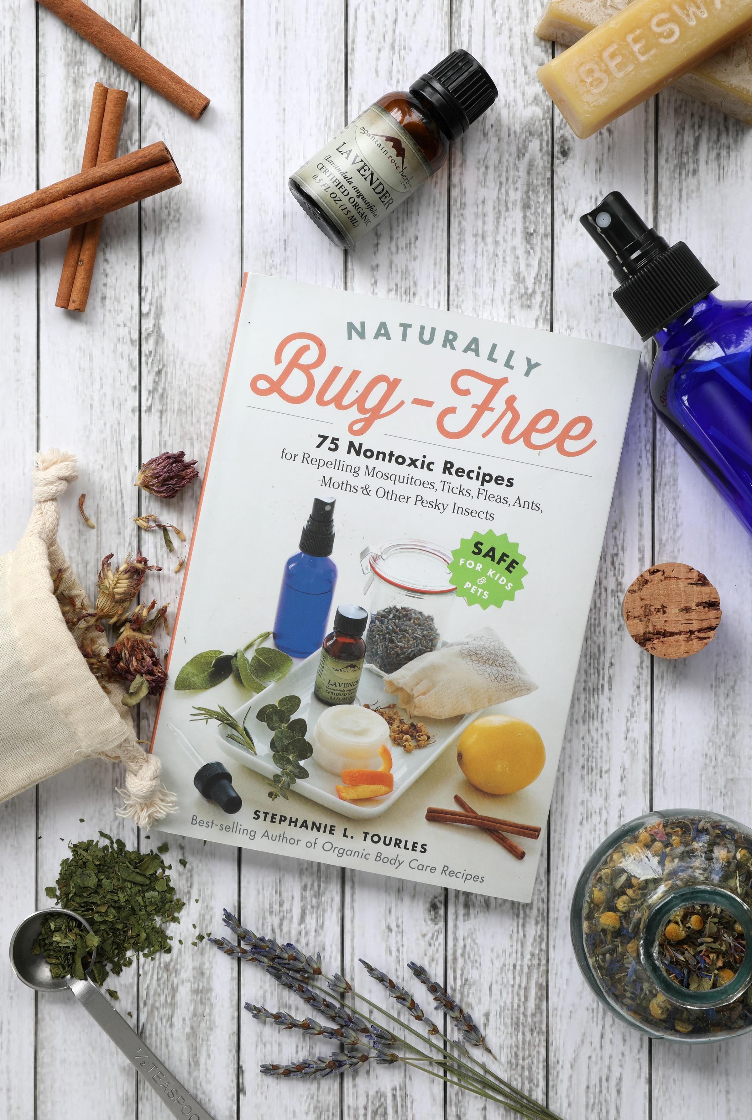 Naturally Bug Gree Recipe Book by Stephanie Tourles sitting around dried herbs and essential oils and beeswax