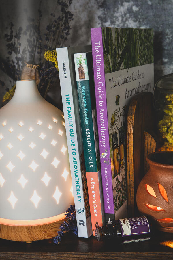 Best books on aromatherapy- set on shelf with diffuser and essential oil bottles
