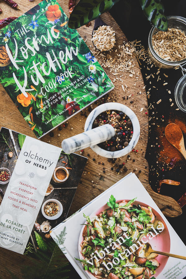 Three favorite books on natural cooking with herb filled mortar and pestle.