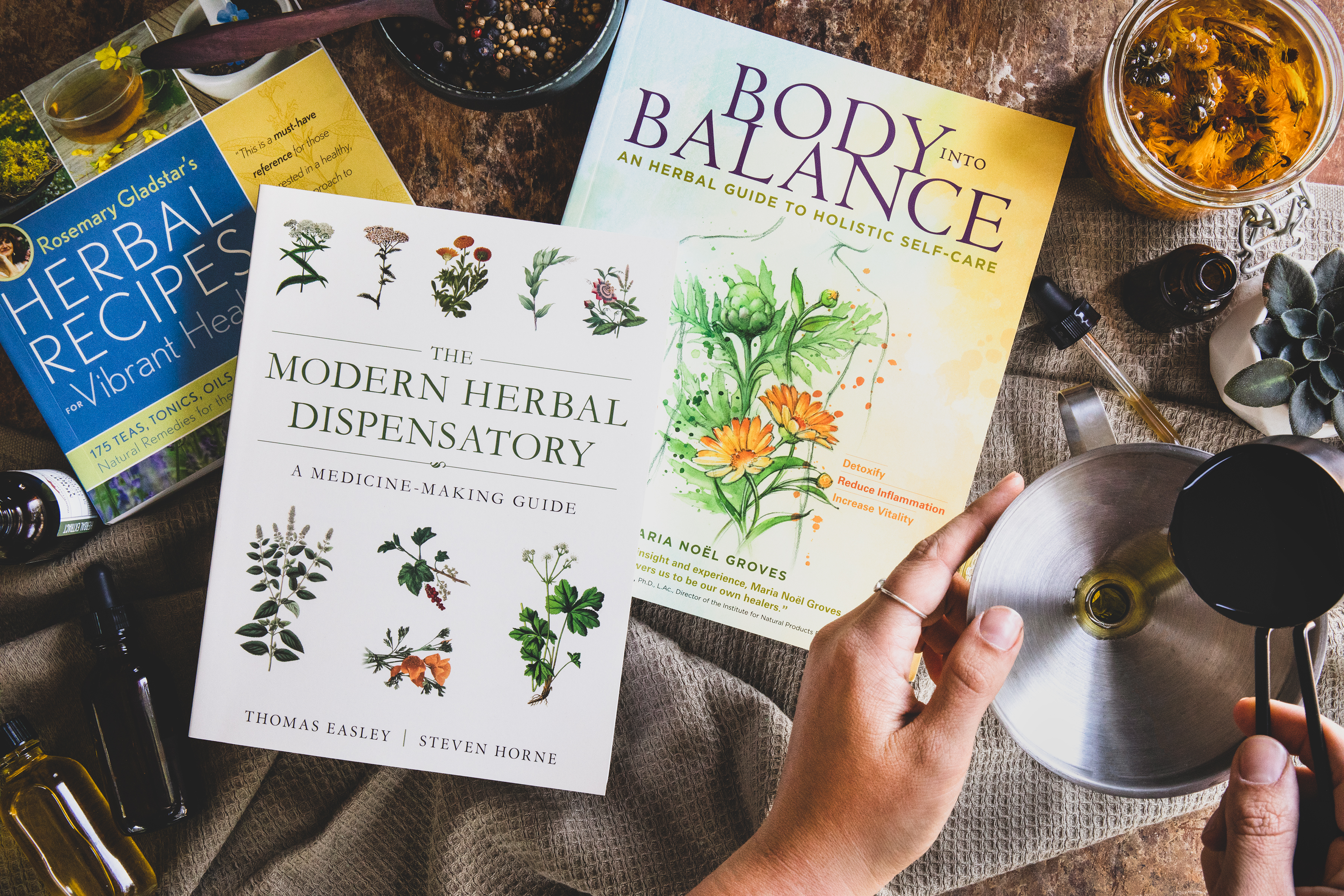 Three favorite books on herbalism with hands working on a recipe.