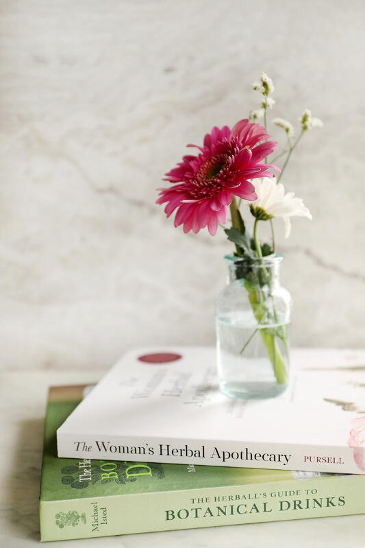 A short stack of books about herbalism with a glass jar full of bright, pink and white, spring flowers.