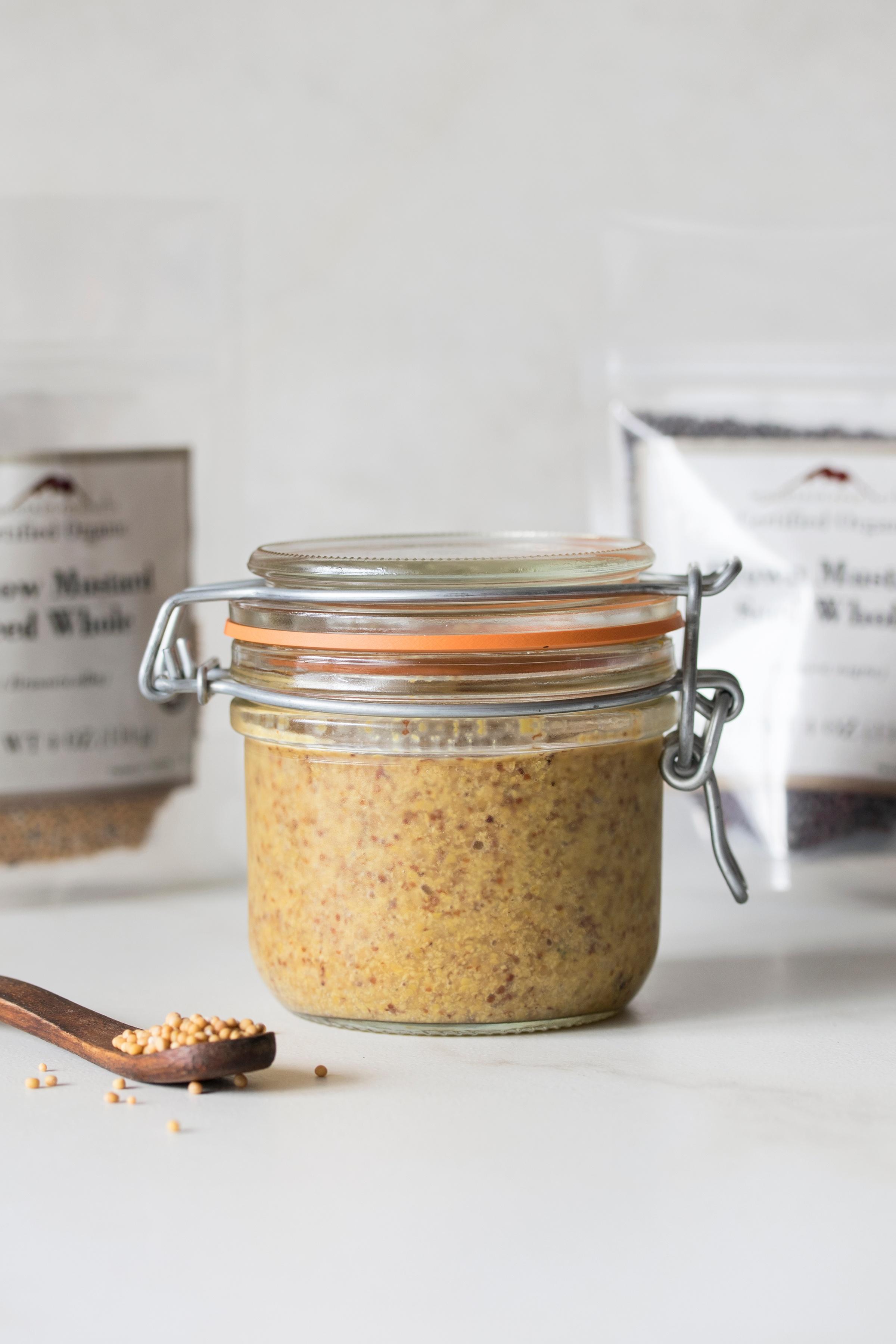 Pantry jar full of mustard with display of ingredients used to make it.